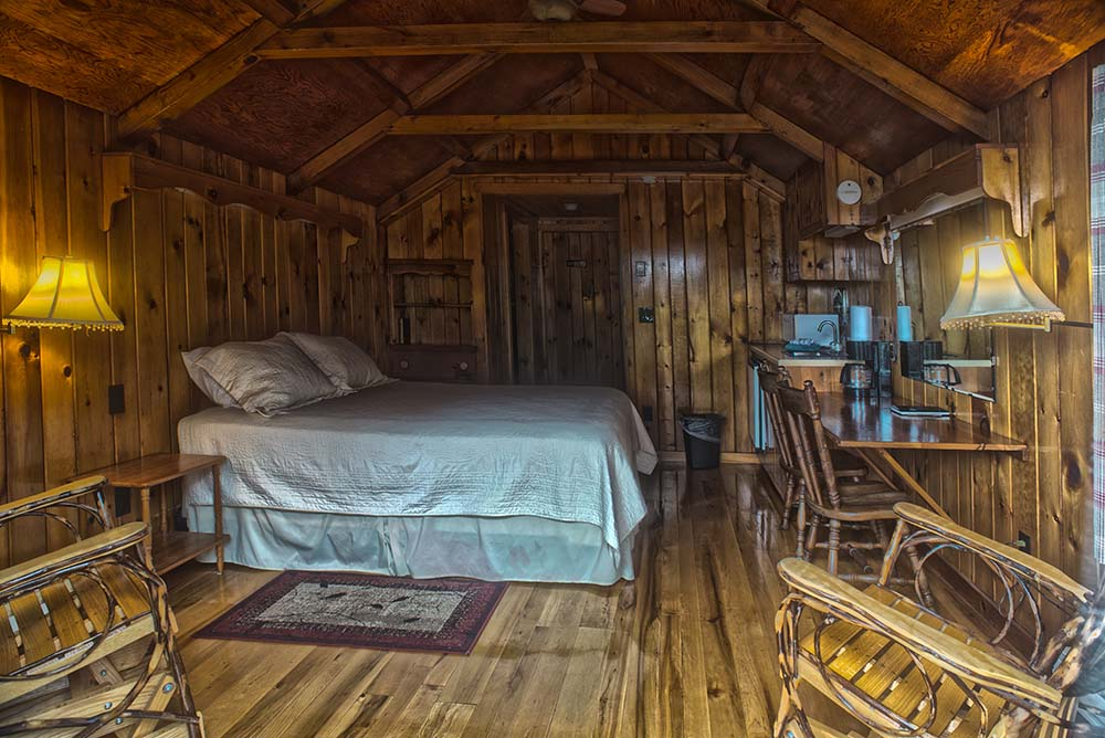 Adirondack style room with chairs and bed