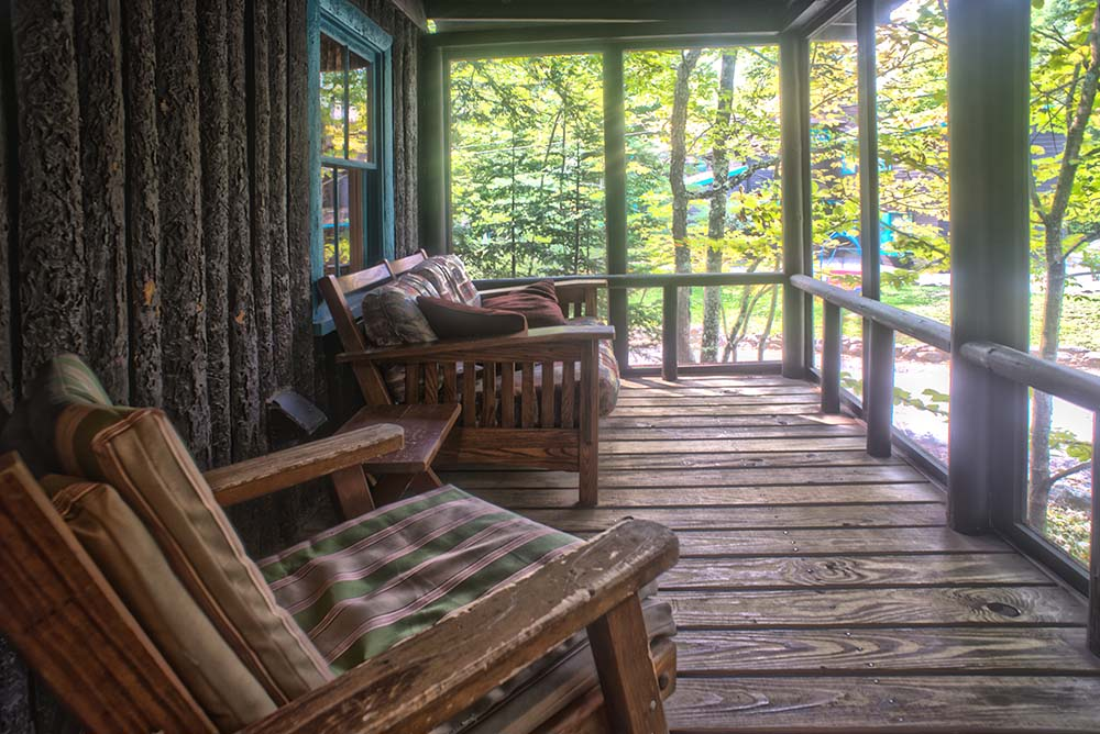 screened in porch with chairs and couch