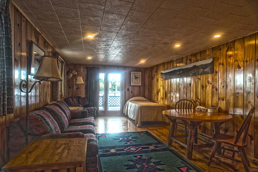 Adirondack style room with couch, bed and table