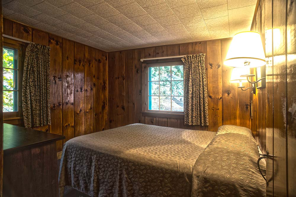 Wood panel bedroom with white blanket on bed